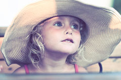 Blond baby girl with summer hat on the beach. Portrait of a blond baby girl on the beach with summer hat Stock Photo