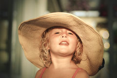 Blond baby girl with summer hat on the beach. Portrait of a blond baby girl on the beach with summer hat Royalty Free Stock Photos
