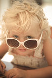 Blond baby girl with sun glasses. Portrait of a blond baby girl on the beach with sun glasses Stock Images
