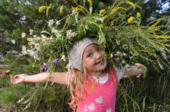Blond baby girl in wreath in home garden Royalty Free Stock Image