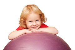 Blond baby playing with fitness ball Royalty Free Stock Photo