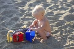 Blond baby playing with toy car on the beach Stock Photos