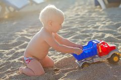 Blond baby playing with toy car on the beach Stock Photo