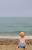 Blond baby sitting on the beach. Blond baby wearing a blue pants sitting on the beach, waitting for someone from the sea on a cloudy day Stock Photography