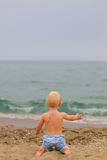 Blond baby sitting on the beach. Blond baby wearing a blue pants sitting on the beach, waitting for someone from the sea on a cloudy day Stock Photos