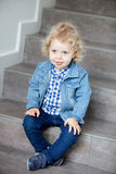 Blond baby sitting on the stairs at home Royalty Free Stock Image