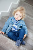 Blond baby sitting on the stairs at home Stock Images