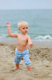 Blond baby standing on the beach Stock Image