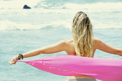 Blond baksida för ung kvinna med öppna armar som tar en siden- torkduk som håller ögonen på havet arkivfoto