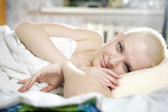 blond bald woman lying on the bed Stock Photos