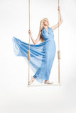 Blond ballerina i blåttklänning på gungor royaltyfria foton