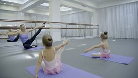 The blond ballet teacher leads the stratching with her two little students in the bright gym. Girls and ballerina sit on the mats with left leg put under the stock footage