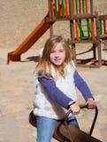Blond barnflicka som leker i lekplatsen som ler på gunga Royaltyfri Bild