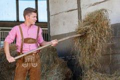 Blond bavarian mężczyzna z pitchfork i sianem fotografia stock