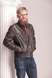 Blond beard man posing near a white column. With his hands in pockets, smiling at the camera Stock Images