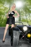 Blond beautiful black sport car young girl. Stand up on forest stock photos