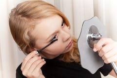 Blond beautiful Caucasian girl paints eyelashes Royalty Free Stock Image