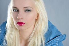 Blond beautiful girl portrait red lips. Blue jacket stock photography