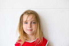 Blond beautiful kid girl smiling on white wall Stock Photos