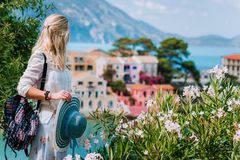 Blond beautiful woman enjoying view of colorful tranquil village Assos on sunny summer travel vacation day. Visiting stock image