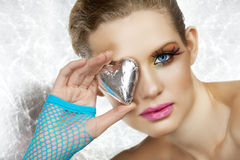 Blond beautiful woman with heart. Blond beautiful woman with blue eyes and fashion make-up holding a silver heart, wearing blue fingerless gloves. Not isolated Royalty Free Stock Image
