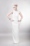Blond beautiful woman in long white dress with creative hairstyl Royalty Free Stock Images