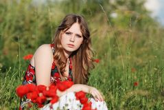 A beauty in a poppy field 4. A blond beautiful young girl sitting in poppy field on a sunny day Royalty Free Stock Photo