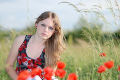 A beauty in a poppy field 3. A blond beautiful young girl sitting in poppy field on a sunny day Stock Images