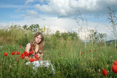 A beauty in a poppy field 1. A blond beautiful young girl sitting in poppy field on a sunny day Stock Photos