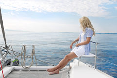 Blond  beautiful young woman on sailing boat. Royalty Free Stock Image