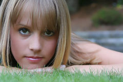 Blond beauty. Outdoor headshot of blond teenage girl lying in the grass Royalty Free Stock Photos