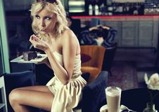 Blond beauty eating a cake Stock Photography