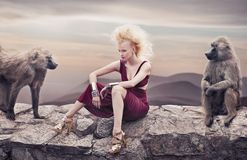 Blond beauty posing with monkeys Royalty Free Stock Photography