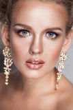 Blond beauty woman portrait with golden hair jewelry and ear-rings Royalty Free Stock Photography