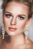 Blond beauty woman portrait with golden hair jewelry and ear-rings Stock Photography