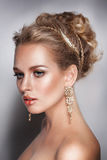 Blond beauty woman portrait with golden hair jewelry and ear-rings Stock Images