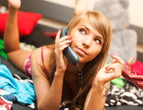 Blond in bed with telephone Stock Images