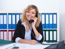 Blond bizneswoman przy biurowym mówieniem z klientem przy telefonem Zdjęcie Stock