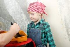 Blond blåögd liten flicka som gör reparationer med fadern i lägenheten royaltyfri fotografi
