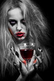 Blond bloody witch. Blond witch with bloody glass on black background, toned image Royalty Free Stock Photos