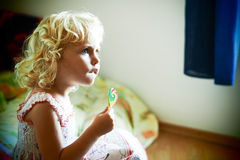 Blond blue eyed baby girl with a candy in her hand Royalty Free Stock Photos