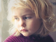 Blond blue eyed little girl looking out the window stock image