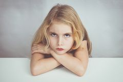 Little girl sitting at a table and looking to me with hate royalty free stock photos