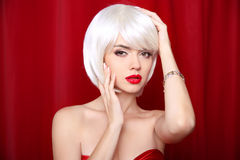 Blond bob hairstyle. Make-up. Beautiful sexy Girl Face Close-up. Red lips. White Short Hair.  Fringe. Vogue Style Woman isolated on curtain or drapes red Royalty Free Stock Image