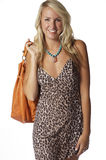 Blond Bombshell. Beautiful blond wearing fun Fall tones and carrying a big orange leather bag Royalty Free Stock Photo