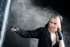 Blond boxing woman in black punching bag Stock Image