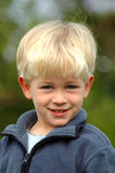 Blond boy. A beautiful clever blond caucasian white boy child head portrait with happy ans smart smiling expression in his handsome face watching outdoors Stock Photos