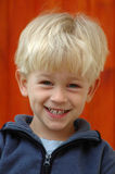 Blond boy. A beautiful clever blond caucasian white boy child head portrait with happy and smart smiling expression in his handsome face watching outdoors Royalty Free Stock Photo