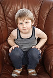 Blond boy in armchair Royalty Free Stock Photos