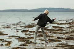 Blond boy on beach throwing a rock. Single blond boy in dark jacket and gray jeans on beach throwing a rock. Small hills on horizon in background Stock Image